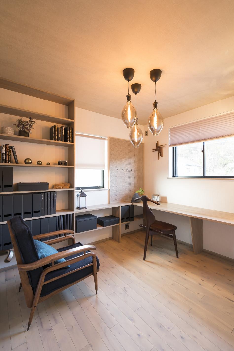 壁一面の収納棚と一体化したデスクの書斎