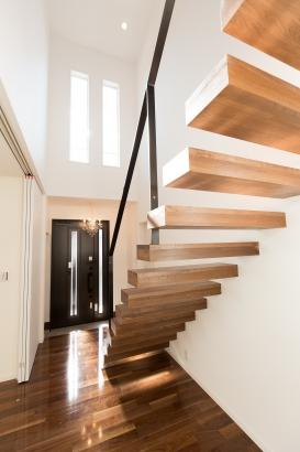 玄関すぐ、迫力ある片持ち階段が来訪者をお出迎え